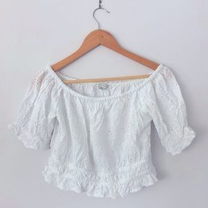 Cropped, white flare tee with detailing.
